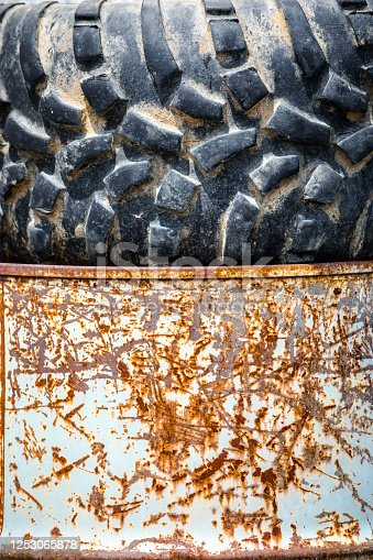 Detail of a truck tire sitting on top of a rusty 55 gallon drum