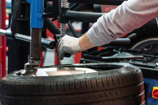 Auto mechanic repairing tire