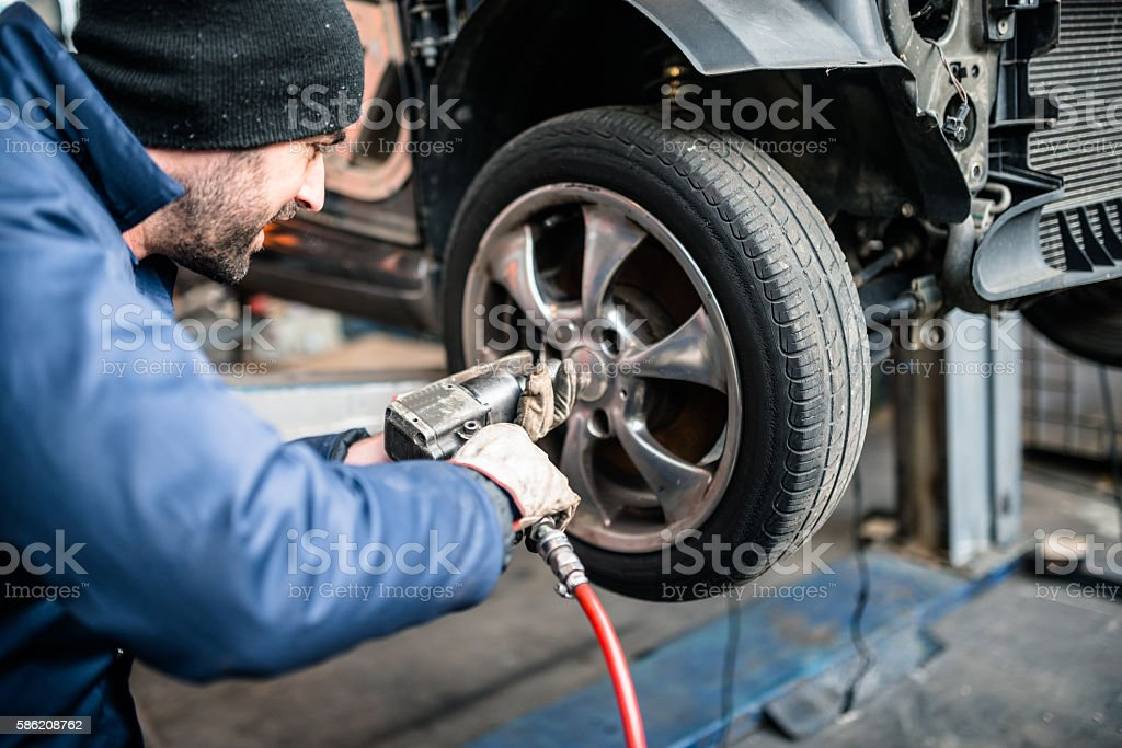 tire repairer changing the car tire stock photo