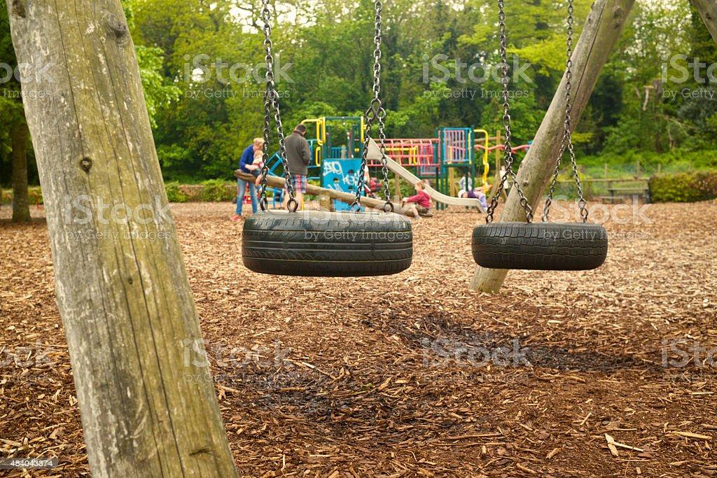 Reifenschaukel im park mit Familie im Hintergrund spielen – Foto