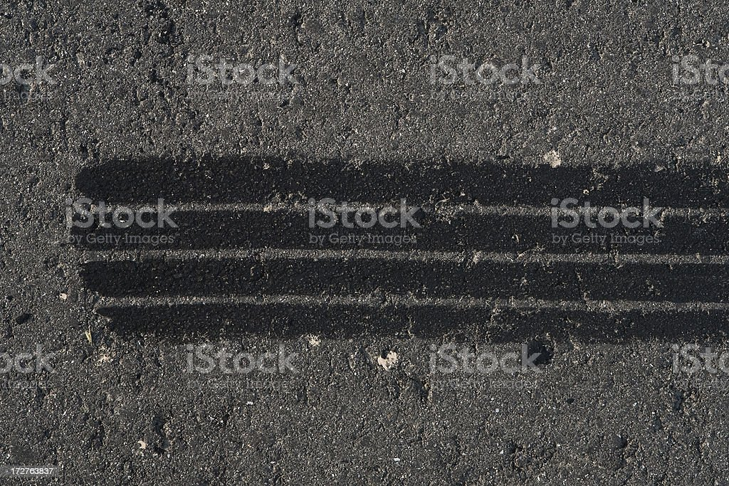 Tire track on weathered asphalt royalty-free stock photo