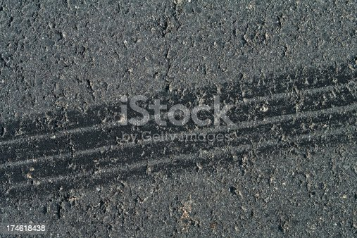 1095367134 istock photo Tire track on weathered asphalt 174618438