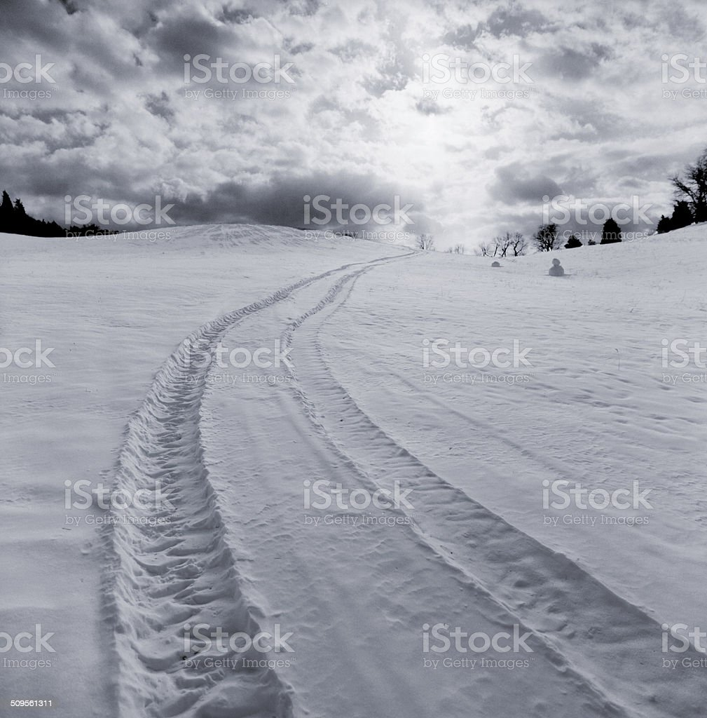 Tire tracks in snow off into distance stock photo