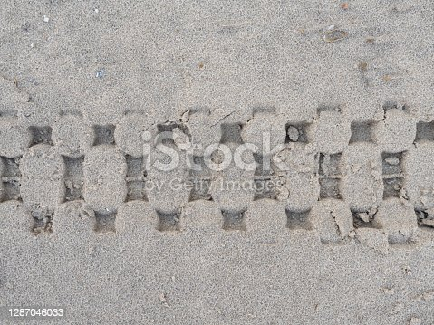 istock Tire tracks of a bicycle in a sandy beach 1287046033