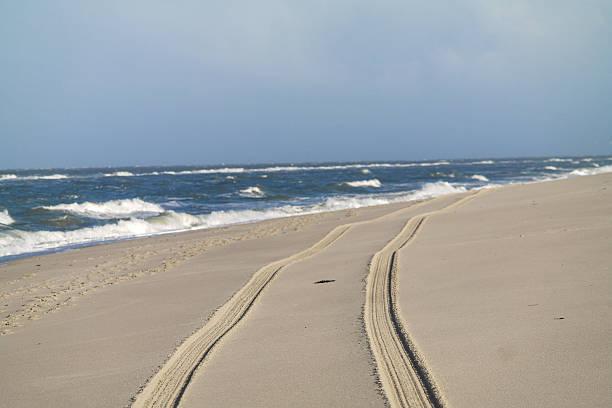 Tire tracks on the beach stock photo