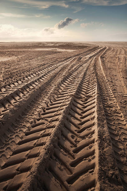 Tire tracks Tire tracks in the sand leading off into the horizon. tire track stock pictures, royalty-free photos & images