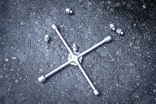 tire wrench and wheel bolts on asphalt