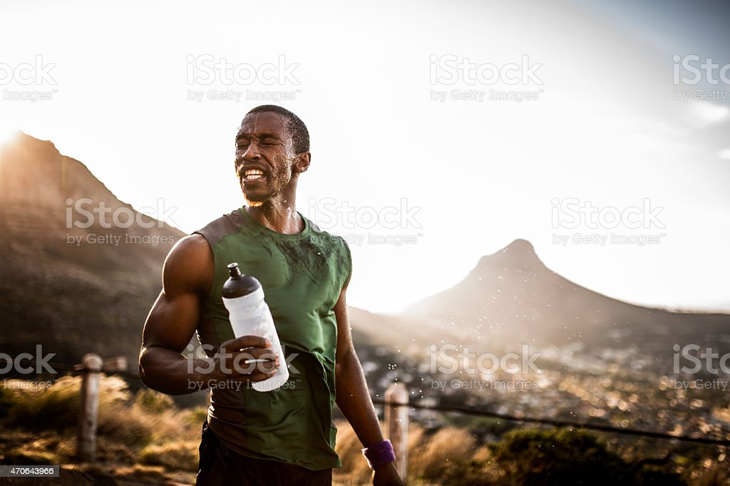Tired African American athlete with water splashed onto his face stock photo
