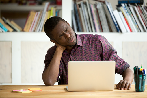 istock Tired African American office worker suffering from neck pain 945838168