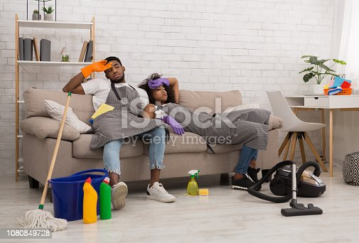 Housekeeping is exhausting. Tired young african-american couple is wiping foreheads while sitting on sofa after cleaning apartment, copy space