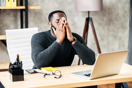 Exhausted African-American office employee sits at the desk with a laptop and covers face with his hands, tired guy closed eye