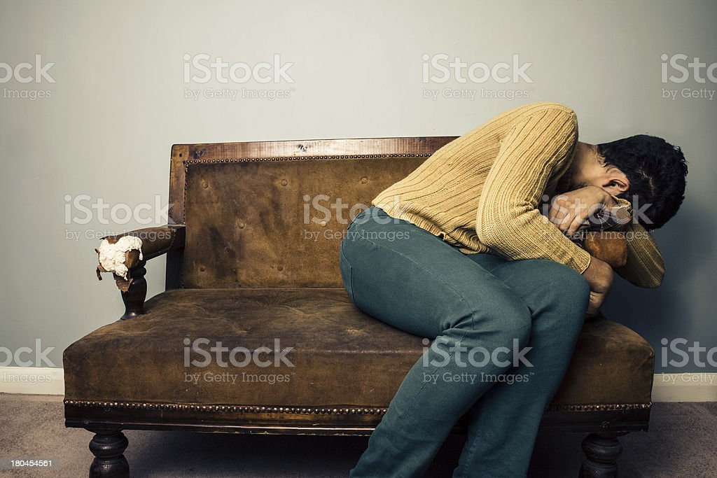 Tired and depressed man hanging off the side of sofa royalty-free stock photo