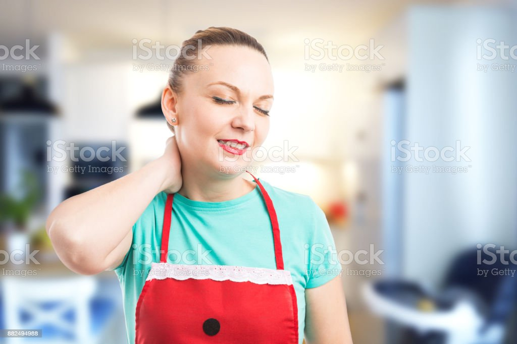 Tired and exhausted housekeeper or maid grabbing scruff stock photo