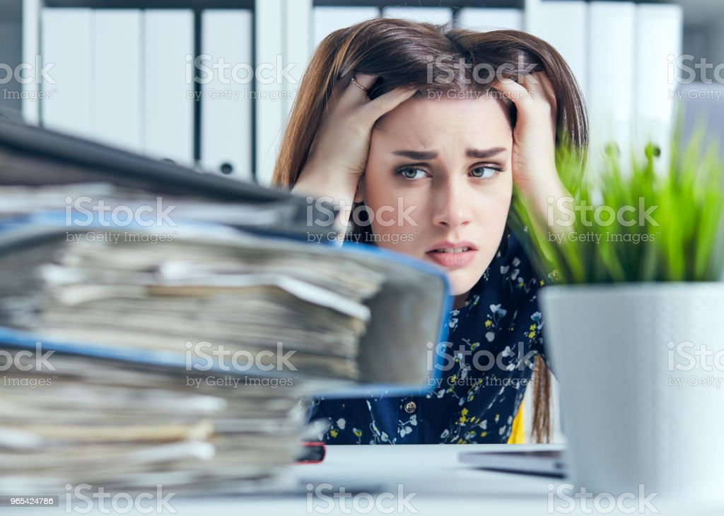 Tired and exhausted woman looks at the mountain of documents propping up her head with her hands royalty-free stock photo