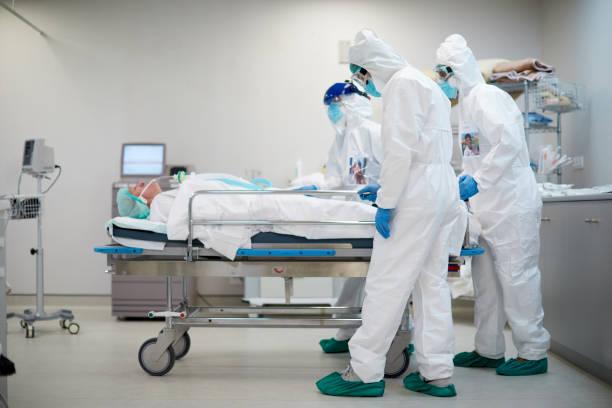 疲倦和悲傷的醫護人員推著醫院 - 死去 個照片及圖片檔