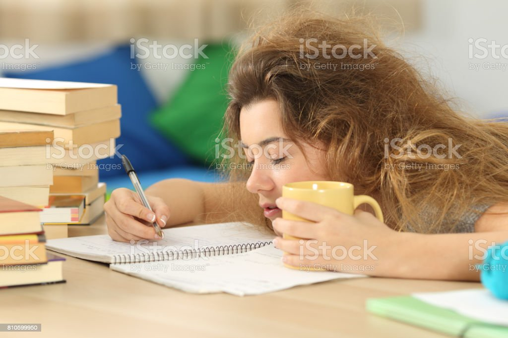 Tired and sleepy student trying to write notes stock photo
