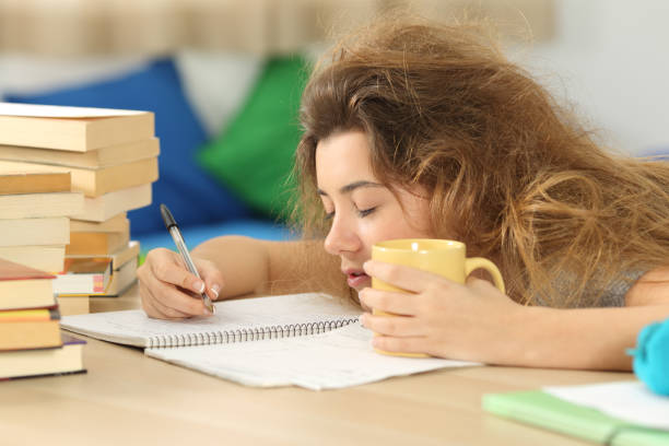 Tired and sleepy student trying to write notes Tired and sleepy student with tousled hair trying to write notes on a desk in her room in a house indoor messy home office stock pictures, royalty-free photos & images