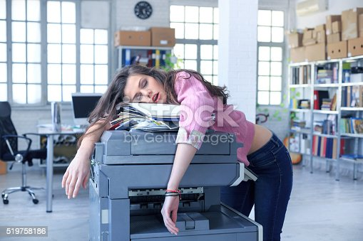 istock Tired assistant sleeping on a copy machine 519758186