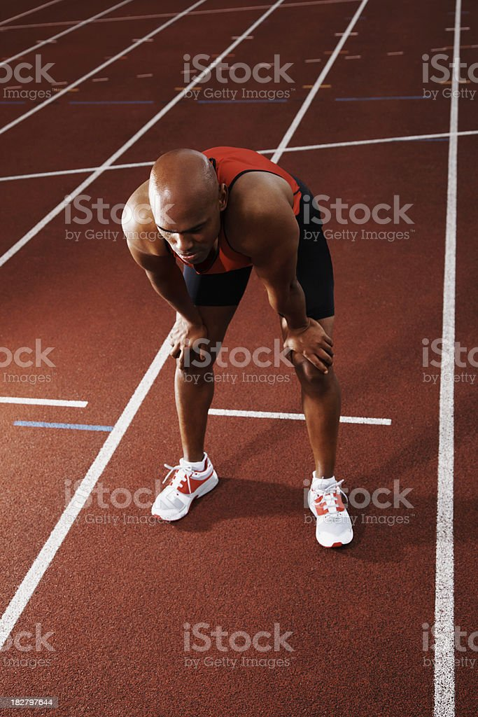 Tired athlete bending on running track royalty-free stock photo