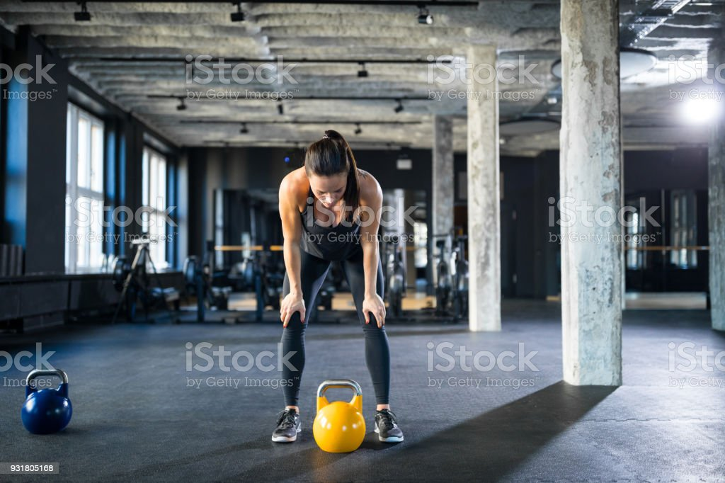 Tired athlete standing with hands on knees in gym stock photo