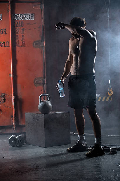 Tired athlete topless wipes the sweat from his forehead stock photo
