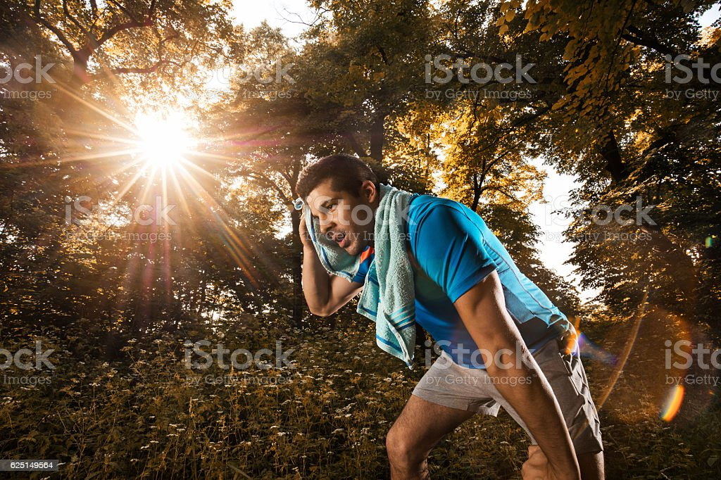 Tired athlete wiping sweat with towel after exercising in nature. stock photo