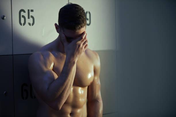 müder athletischer mann, der nach anstrengendem sporttraining kopfschmerzen hat. - mit muskelkater trainieren stock-fotos und bilder
