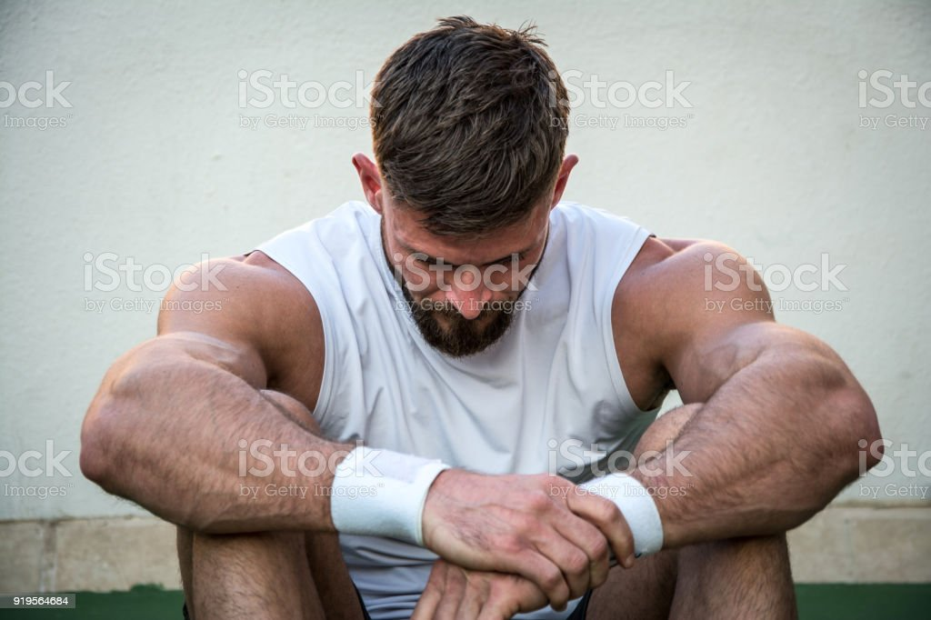 Tired athletic man looking down after intensive fitness workout. stock photo