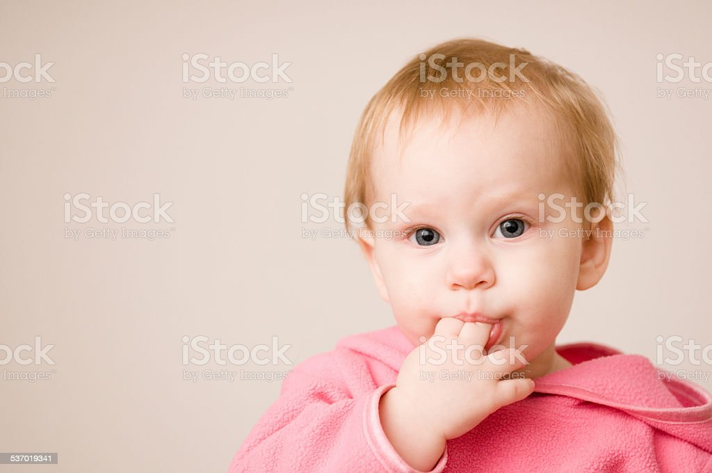Tired Baby Girl Sucking on Her Fingers stock photo