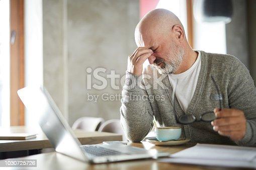 Tired senior freelancer rubbing eyes