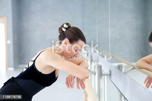 istock Tired ballerina has break in dance workout in ballet class room. Girl is putting hands on barre in front of mirror. 1159176735