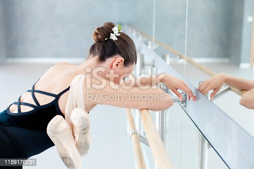 istock Tired ballerina with pointe shoes has break in dance workout in ballet classical school. Girl is putting hands and head on barre in front of mirror. 1159176731