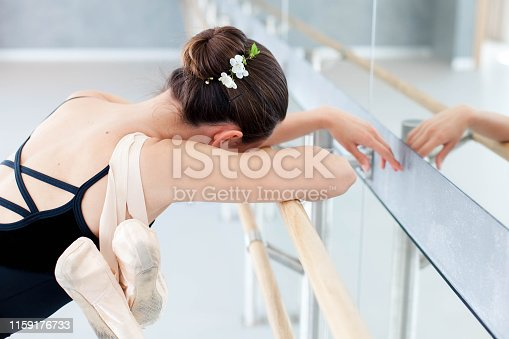 istock Tired ballerina with pointe shoes has rest in dance practice in ballet classical school. Girl is putting hands and head with spring flowers on barre. 1159176733