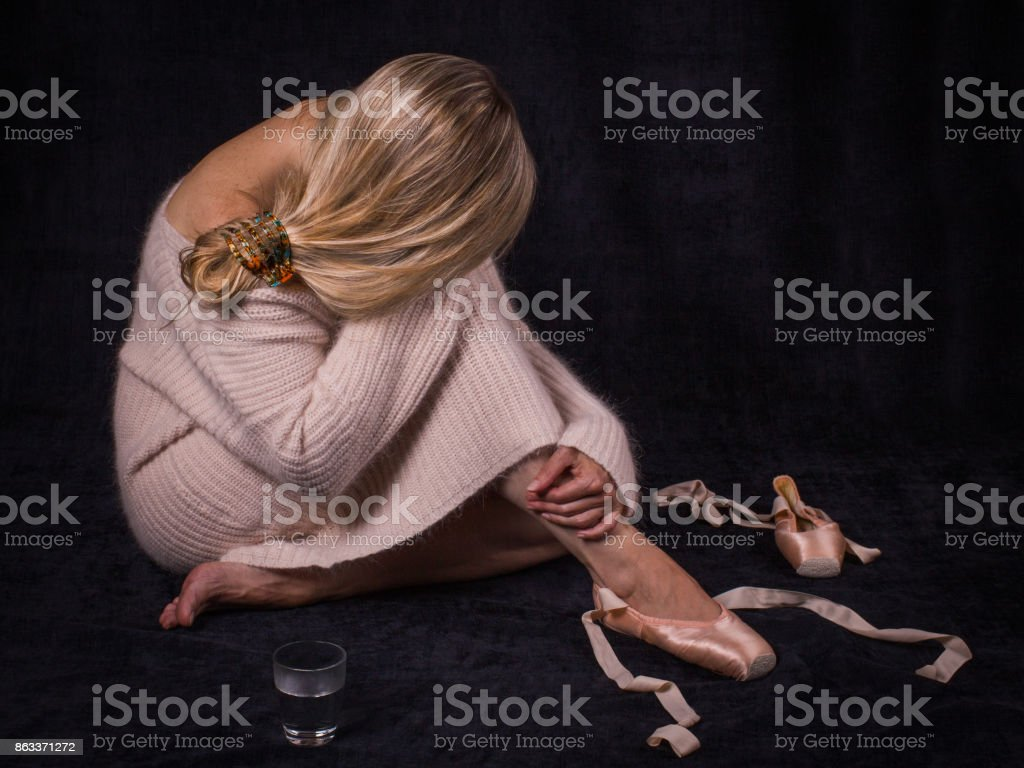 Tired ballet dancer sitting  with an inclined head. stock photo