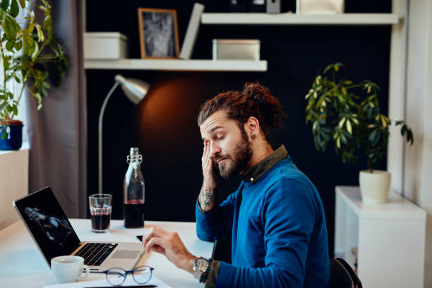 Tired bearded hipster sitting in his office and rubbing his eyes. stock photo