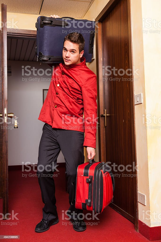 Tired Bellboy with Luggages stock photo