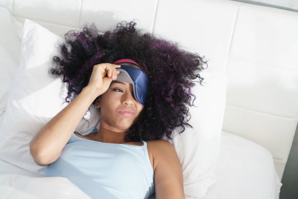 Tired Black Girl Waking Up In Bed With Sleep Mask stock photo