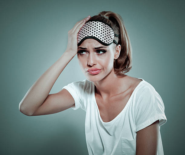 Tired blonde woman wearing sleeping mask on her forehead Conceptual portrait of tired blonde young woman wearing white t-shirt and sleeping mask on her forehead, suffering from headache. Standing against grey background with hand on her head. Studio shot. jet lag stock pictures, royalty-free photos & images