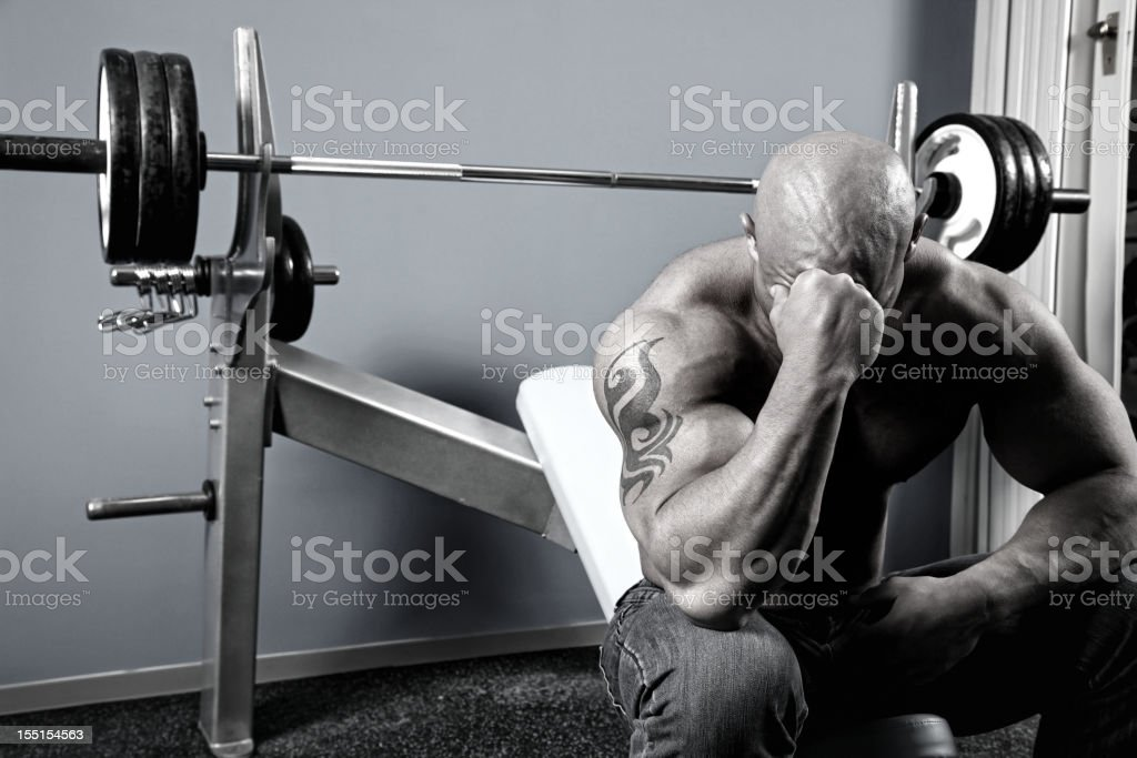 Tired bodybuilder sitting on a bench in gym royalty-free stock photo