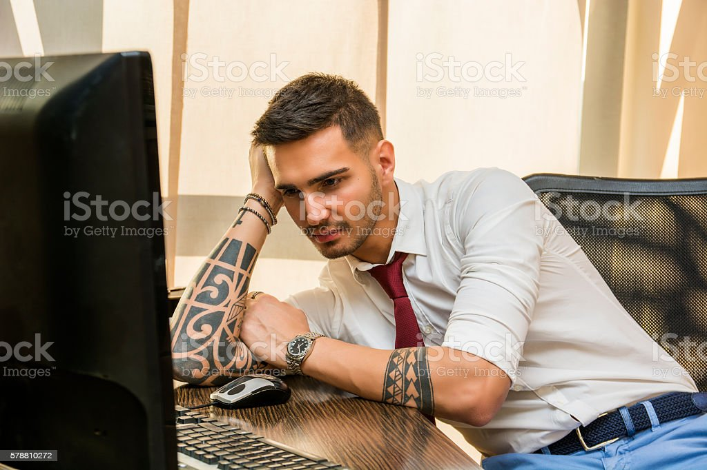 Tired bored young businessman sitting in office stock photo