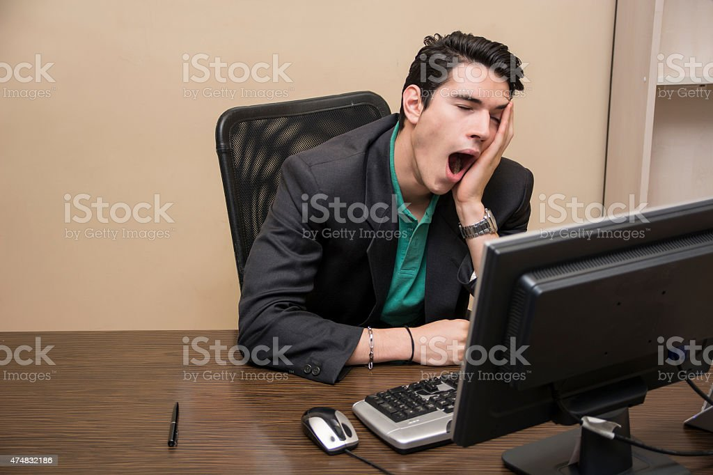 Tired bored young businessman sitting in office yawning stock photo
