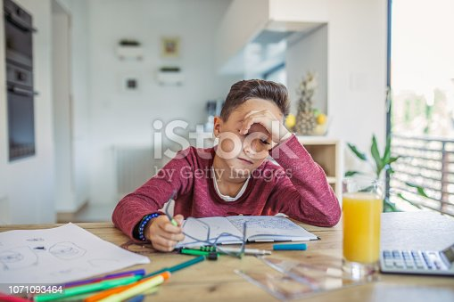 Tired boy doing his homework at the table