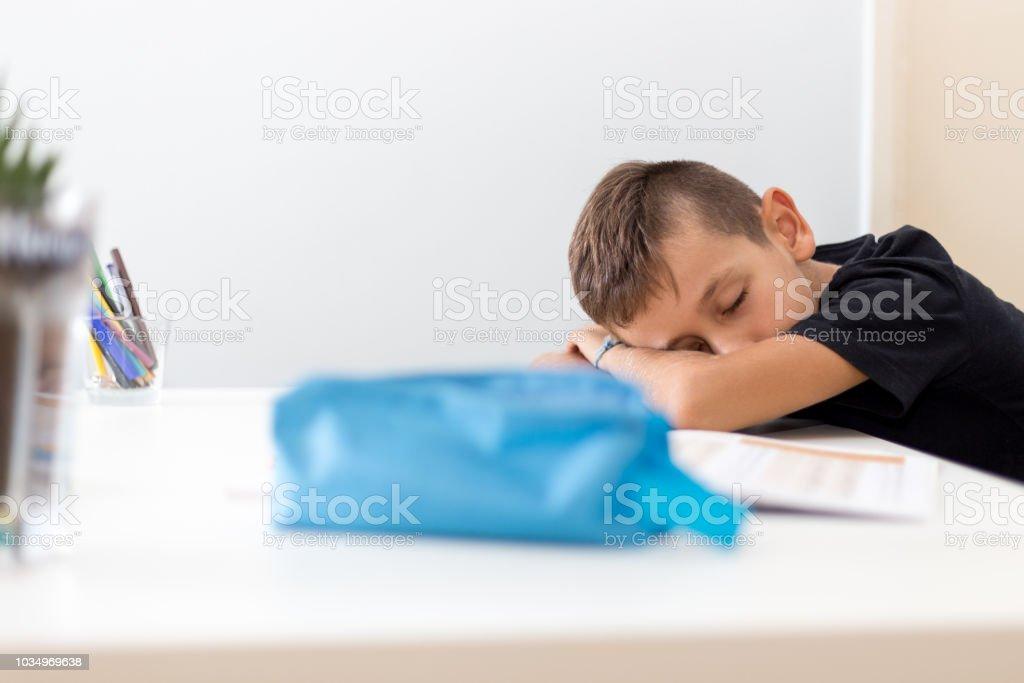 Tired boy falls asleep while doing his homework stock photo