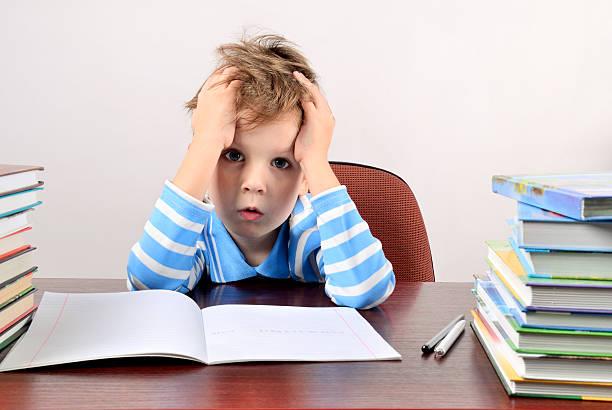 Müde Junge, sitzen an einem Schreibtisch und Hände halten head – Foto