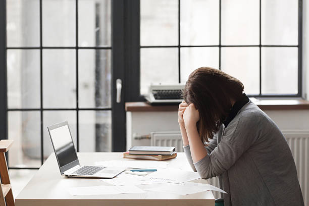 Tired business woman at workplace in office Tired business woman at workplace in office, holding her head in hands. Overworking, making mistake, stress, depression concept downsizing unemployment stock pictures, royalty-free photos & images
