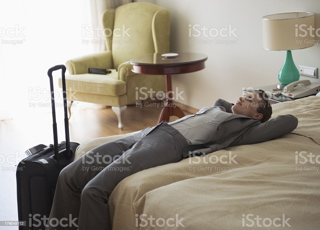 Tired business woman laying on bed in hotel room royalty-free stock photo