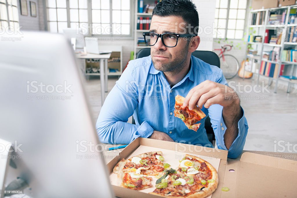 Tired businessman eating pizza at the office stock photo