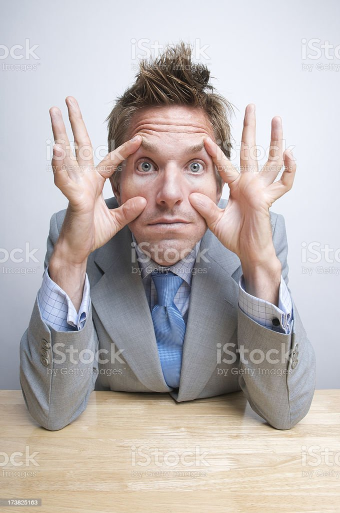 Tired Businessman Office Worker Propping His Eyes Open at Desk stock photo
