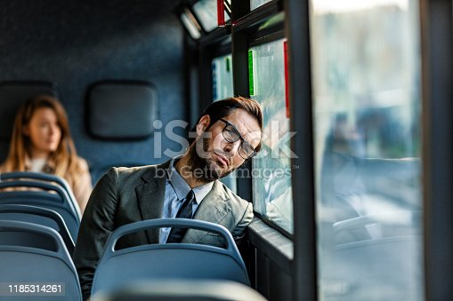 Tired young businessman sitting on the bus and day dreaming while leaning on the window during the day.