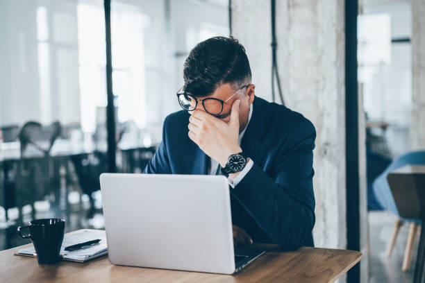 Tired Businessman Mid adult businessman look tired in the office head in hands stock pictures, royalty-free photos & images